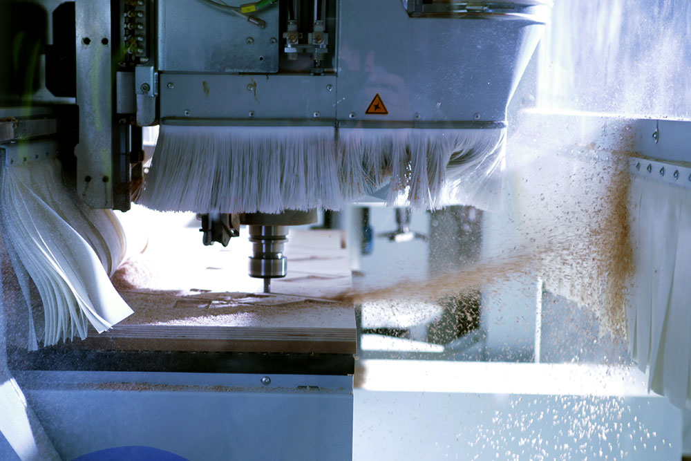 CNC router performing a cutting operation with the extraction removed for inspection, throwing up a plume of sawdust