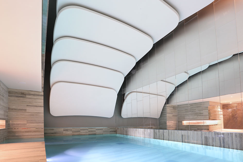 Ceiling panels moulded from machined wood formers mounted in the roof of a private swimming pool