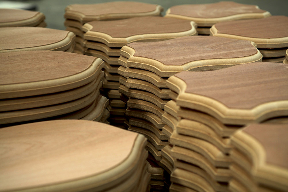 Stacked up production run of machined wood crest-shaped plaques