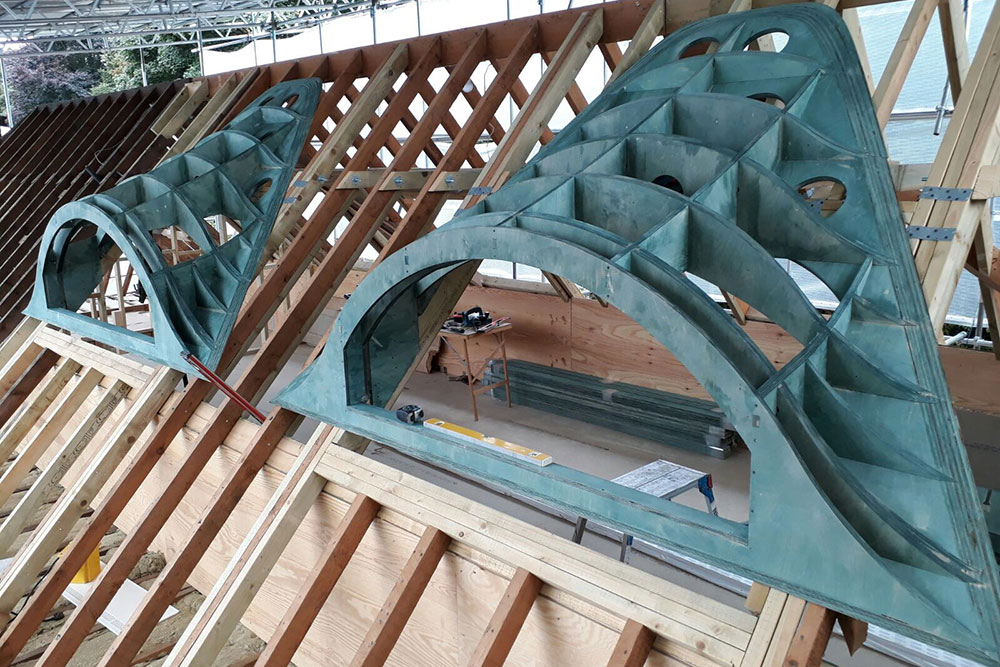 Engineered wood structural framework for curved dorma windows assembled on pitched roof trusses